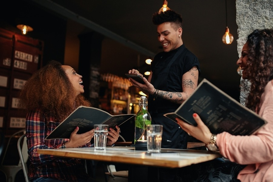 Young Women Placing Order To A Waiter At Cafe
