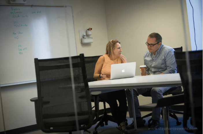 two upserve employees editing on computer
