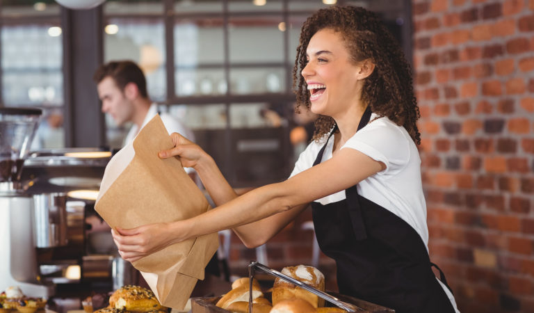 Cafe employee giving customer a bag of baked goods