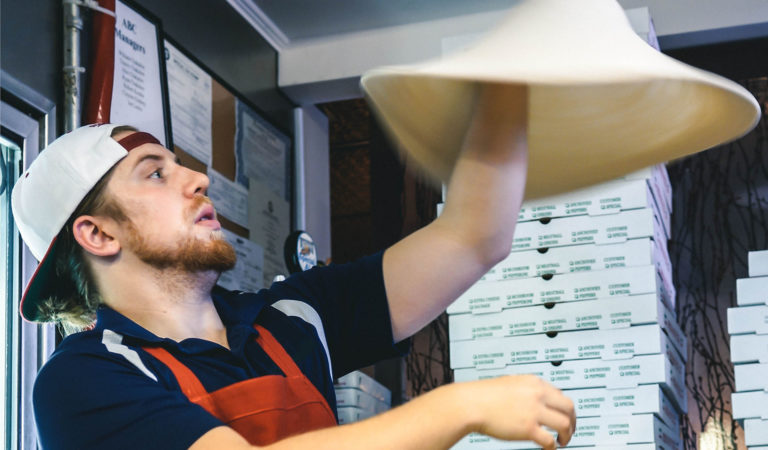 Pizza employee tossing dough while his company runs on a pizza pos