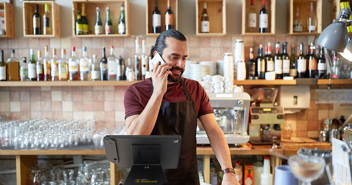 server on phone in front of restaurant pos system