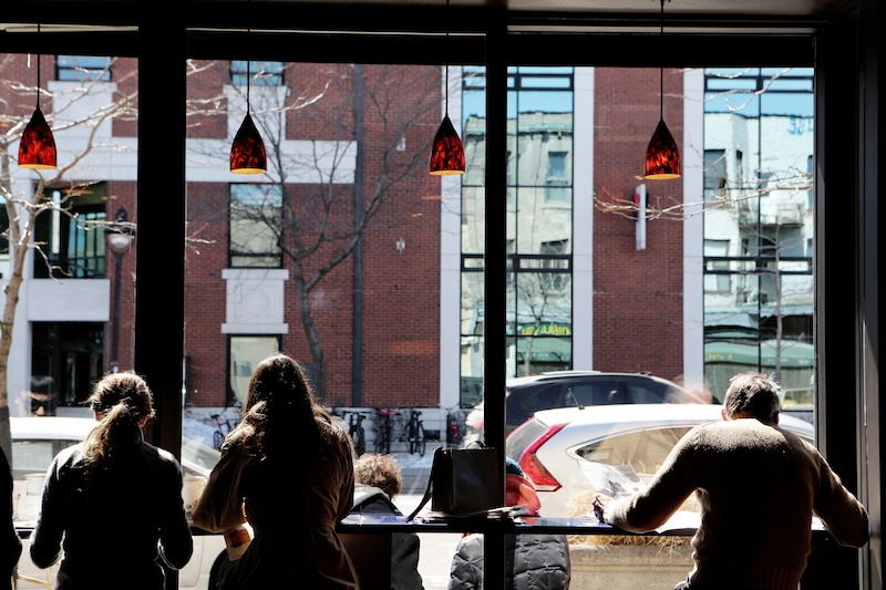 people doing work at coffee shop looking outside