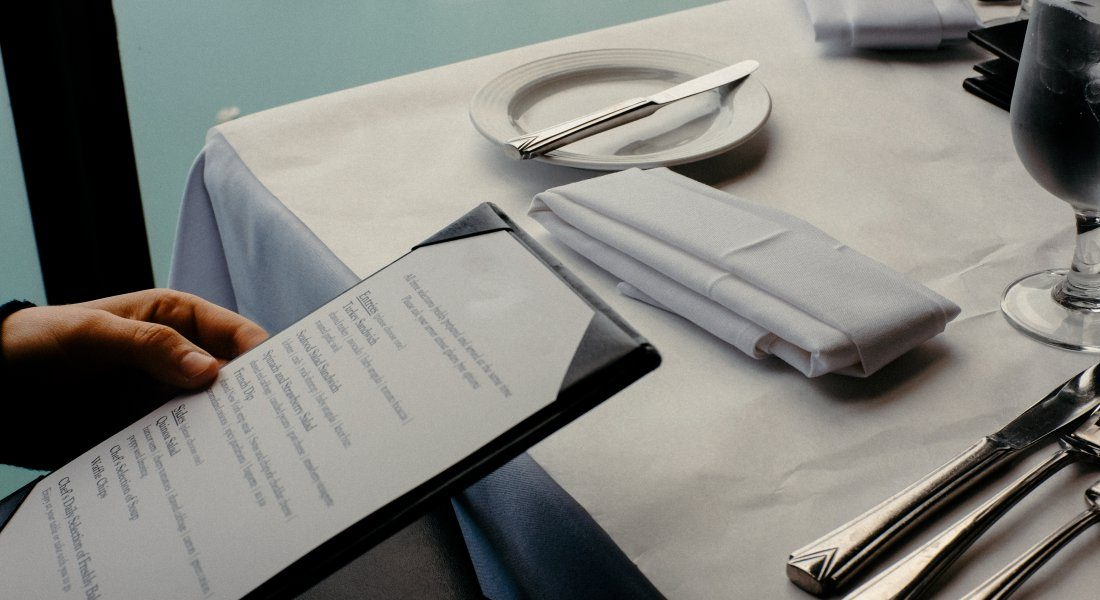 restaurant menu on a table with a place setting