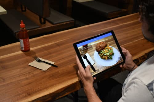 A customer peruses an augmented reality menu