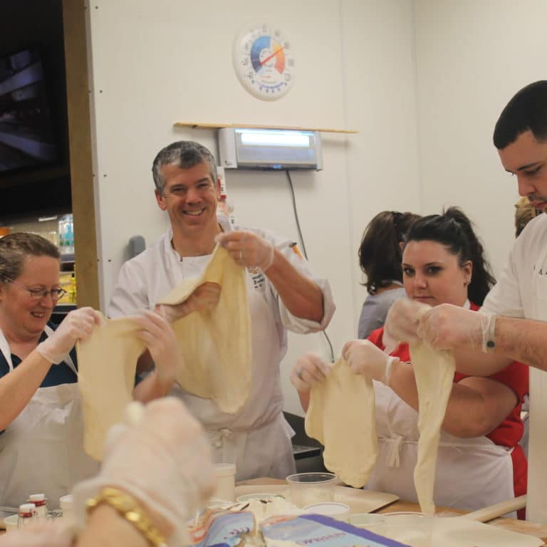 Executive chef Joe Brenner at working with staff at Tuscan Kitchen's La Scuola Culiaria.png