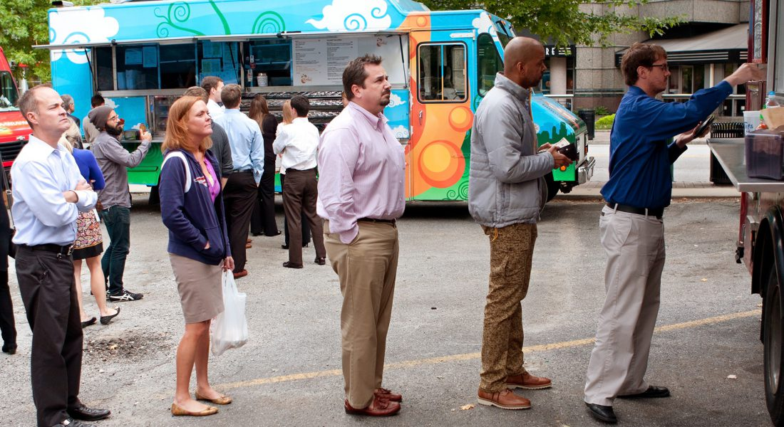 people waiting in line for food trucks