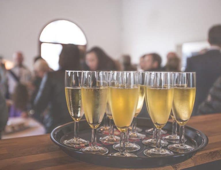 sparkling wine glasses on platter with a blurry backgrounf