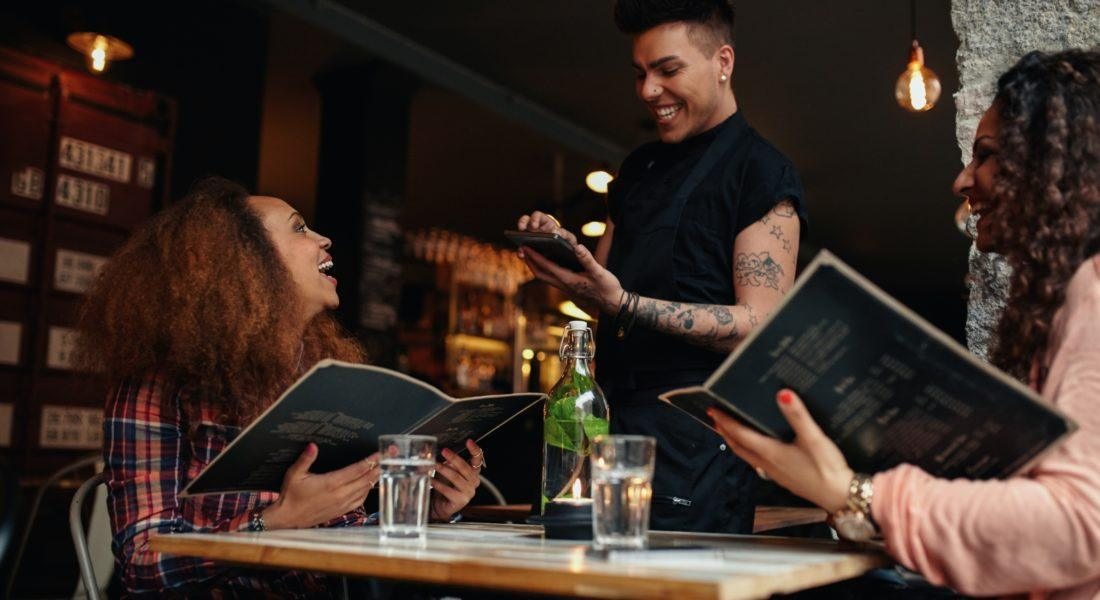 waitress taking orders from group of friends at table