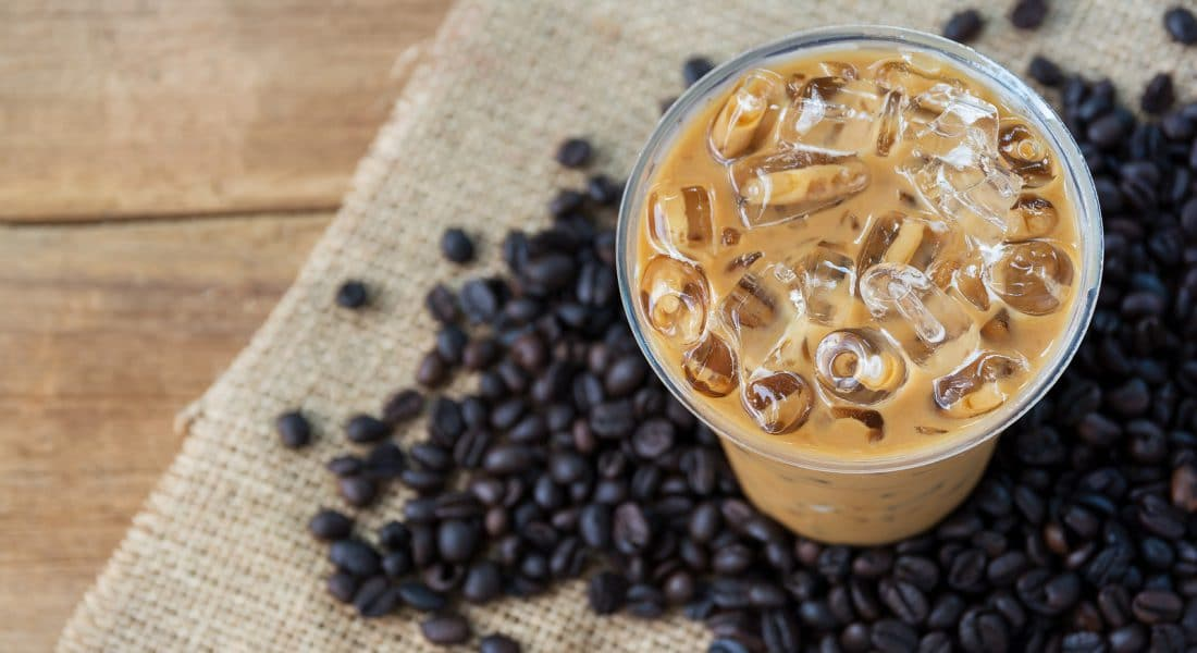 top view cold Ice coffee with fresh coffee on a wooden background