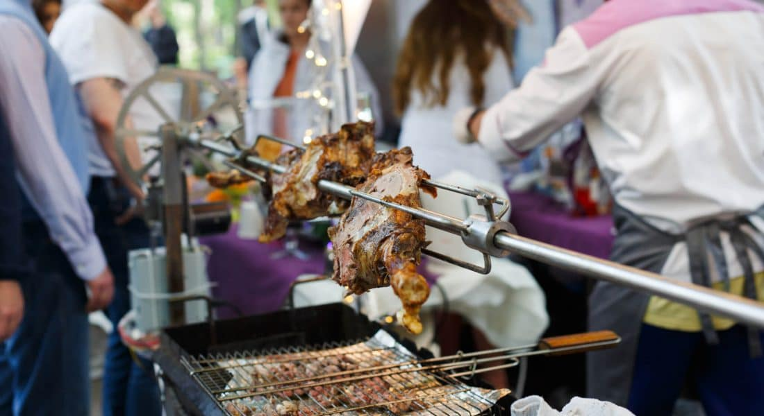 Meat barbecue picnic at country fair. Lamb leg roasted at spit. Lamb grill, big piece of meat at rolling skewer. Street vendor,