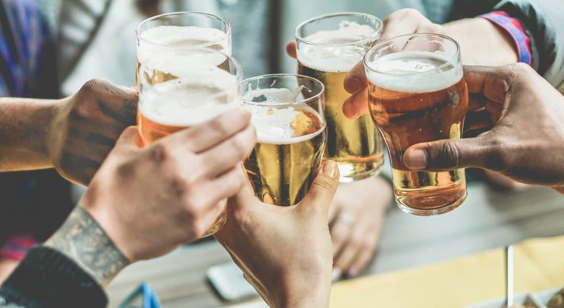 Multiracial group of friends enjoying a beer - Young people hands toasting and cheering aperitif beers half pint - Friendship and youth concept - Warm vintage filter - Focus on bottom hand