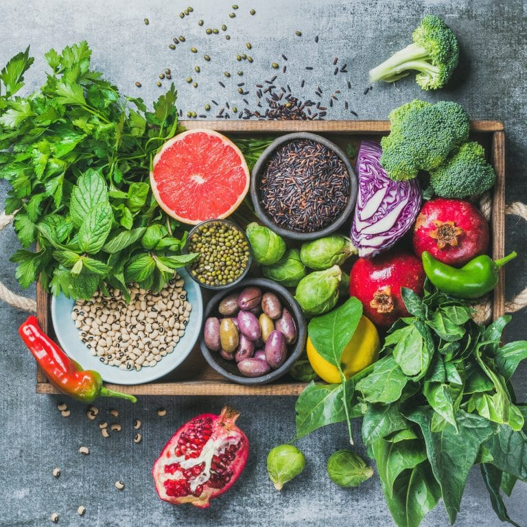 Vegetables, fruit, seeds, cereals, beans, spices, superfoods, herbs, condiment in wooden box for vegan, gluten free, allergy-friendly, clean eating or raw diet.