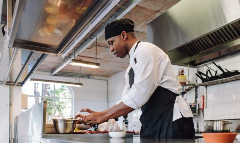 Restaurant chef preparing food. Chef working in a commercial kitchen.