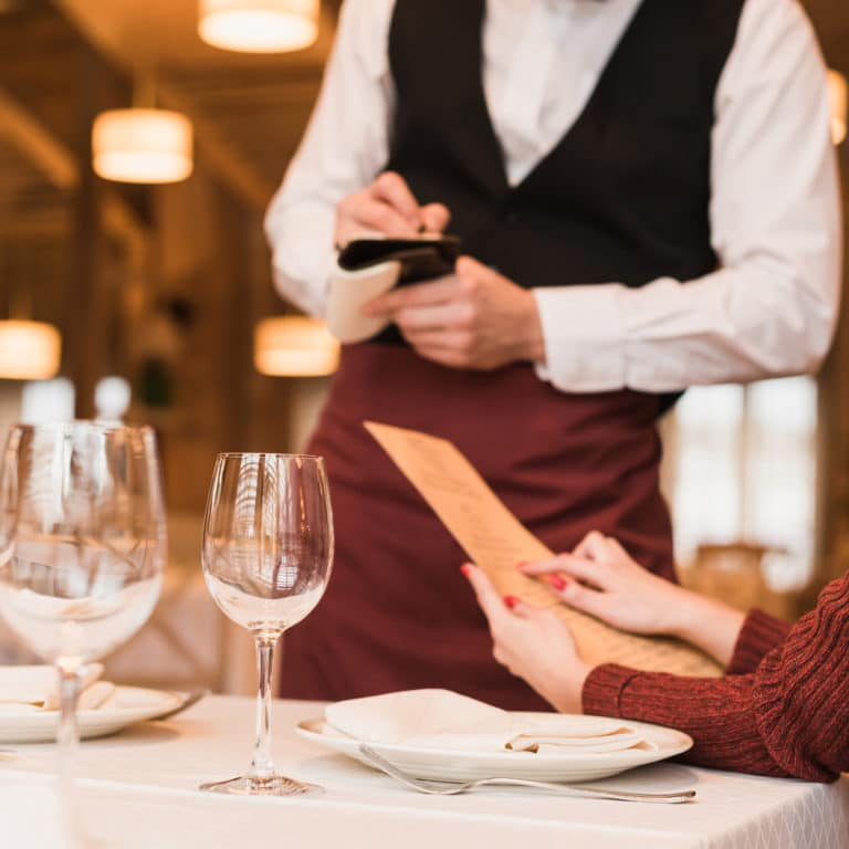 Waiter writing down the order of customer at the restaurant