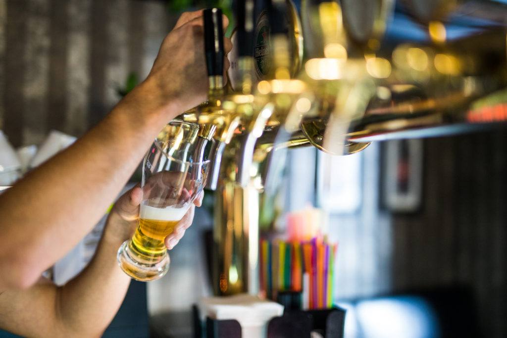 barman hand at beer tap pouring draught lager beer serving in a restaurant or pub.