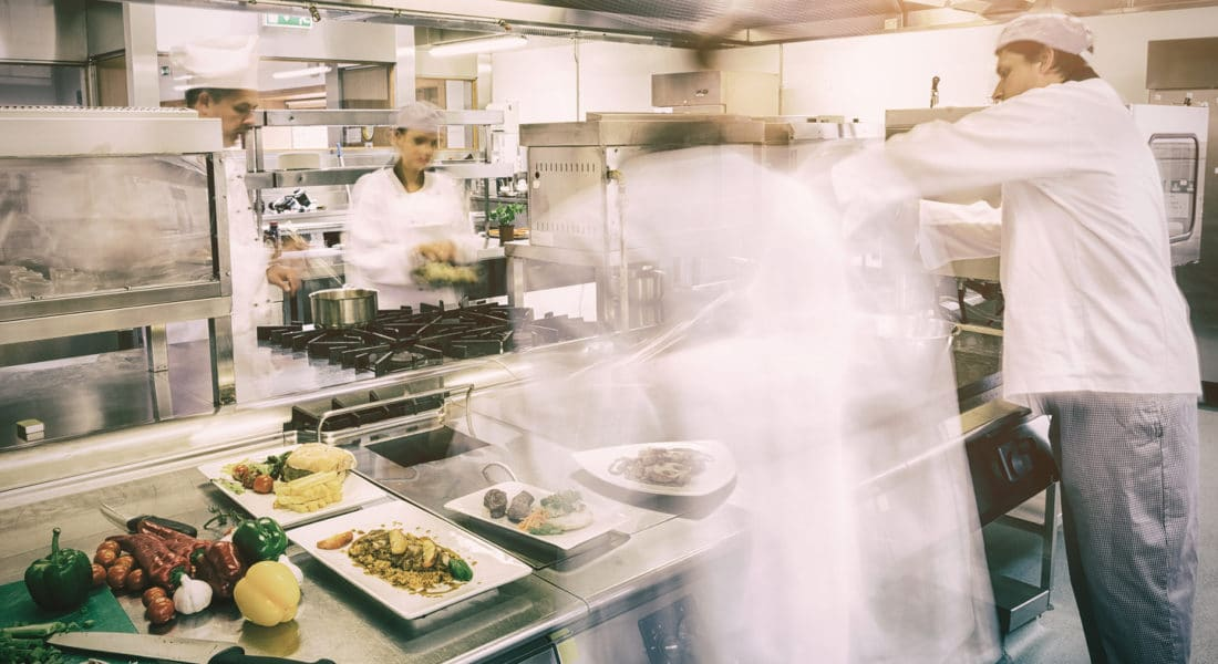 Chefs busy at work in professional kitchen