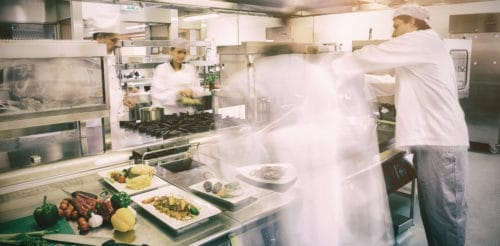 Chefs busy at work in professional restaurant kitchen