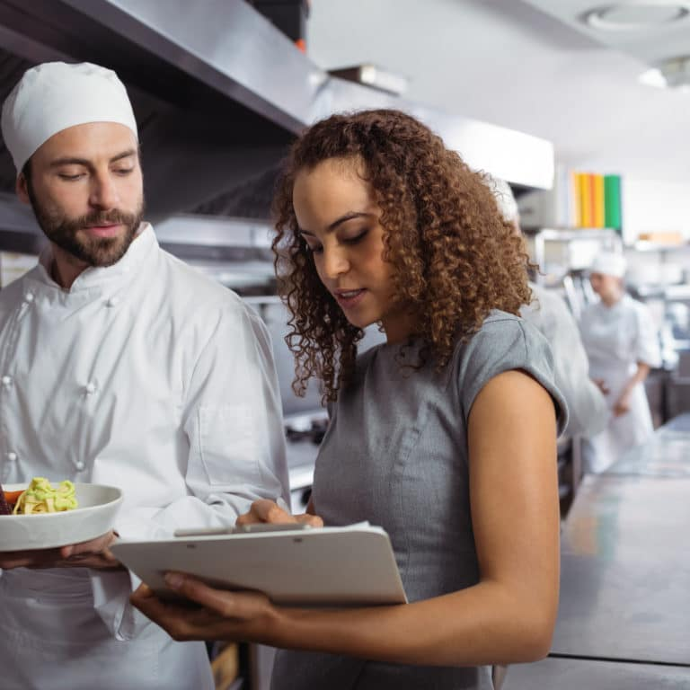 Chefs discussing optimized menu on clipboard in commercial restaurant kitchen