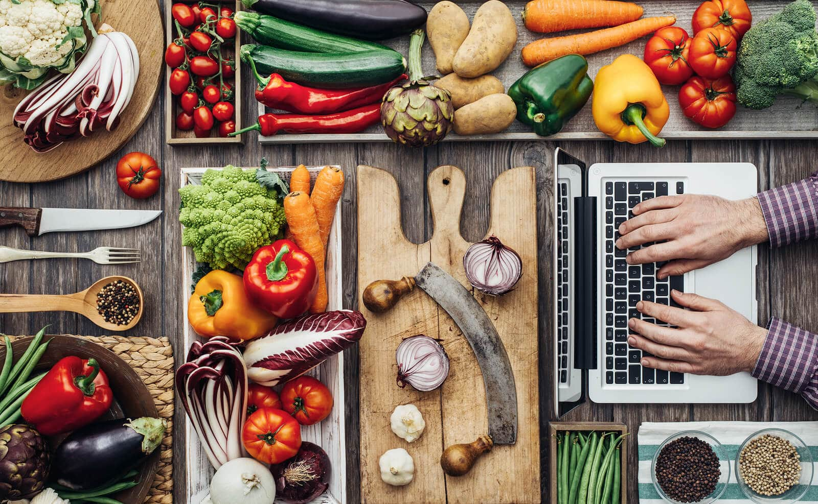 Freshly harvested vegetables cooking utensils and a laptop on a rustic kitchen worktop a man is searching recipes online