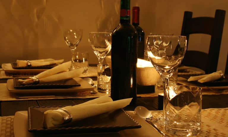 Table set for dinner with candles and wine.