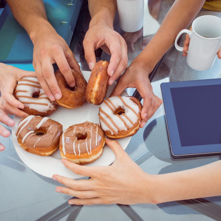 a bunch of hands reaching for donuts at the same time with a coffee cup in the image