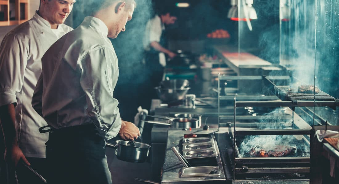 Two chefs in a restaurant cooking foods