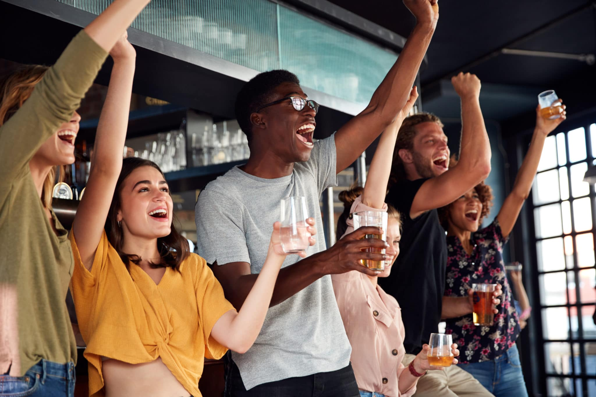 Group Of Male And Female Friends Celebrating Whilst Watching Game