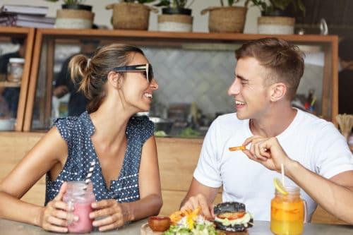 Happy couple having lively conversation on their first date having joyful and carefree expressions looking at each other and laughing. Man in white t-shirt sharing positive news with woman in shades in restaurant