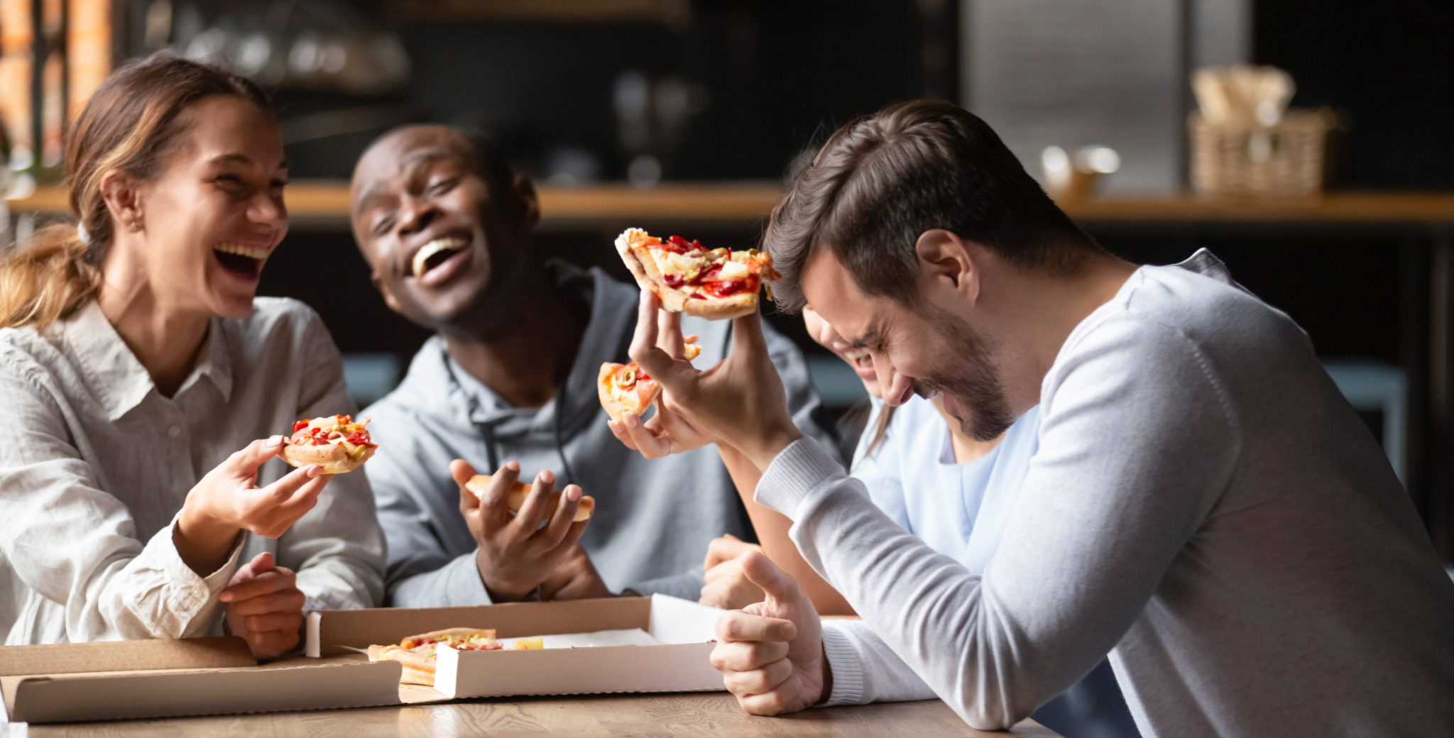 Happy multiracial friends enjoy tasty pizza from takeaway delivery