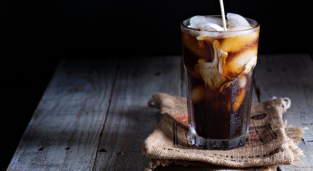 Cold brew coffee in a tall glass on a burlap napkin with a dark background