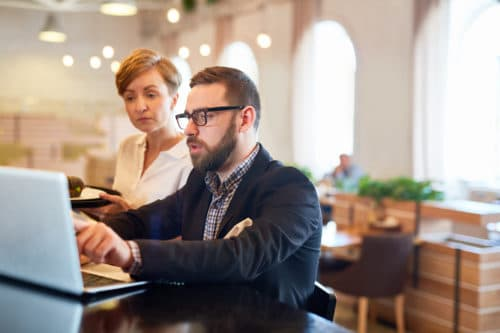 Owner of restaurant explaining changes in online optimized restaurant menu to waitress