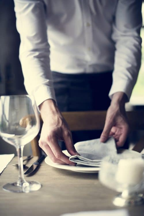 restaurant staff setting a table