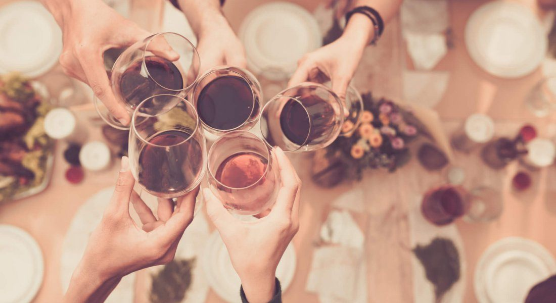 Friends clinking glasses with wine above dinner table