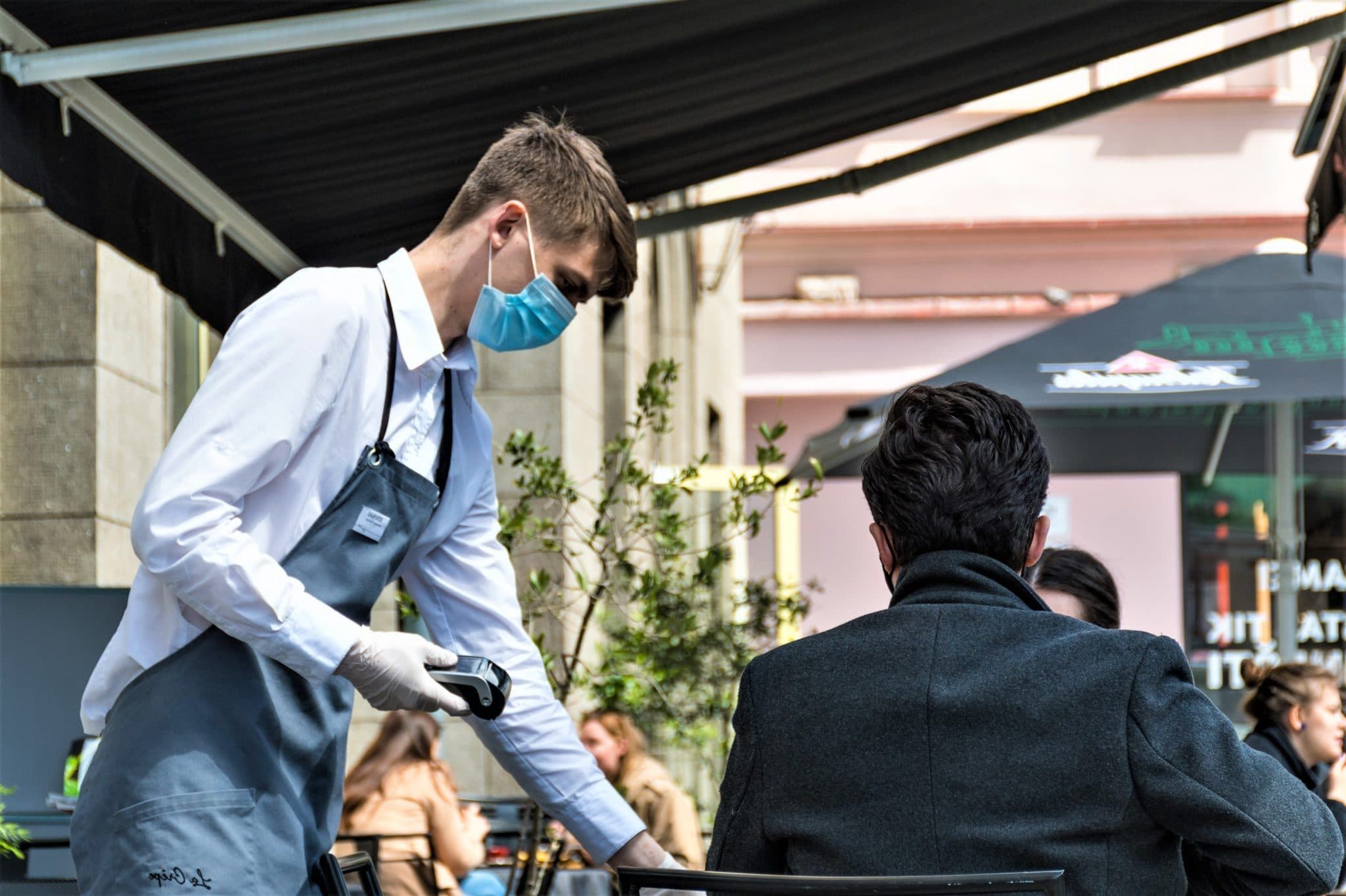 Vilnius, Lithuania - May 15 2020: Waiter with a mask and gloves and client at the table of an outdoor bar, cafe or restaurant, reopening after quarantine