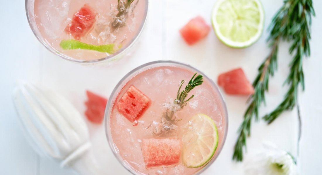 Watermelon fruity cocktail mocktail drink decorated with cubes of fresh watermelon and rosemary