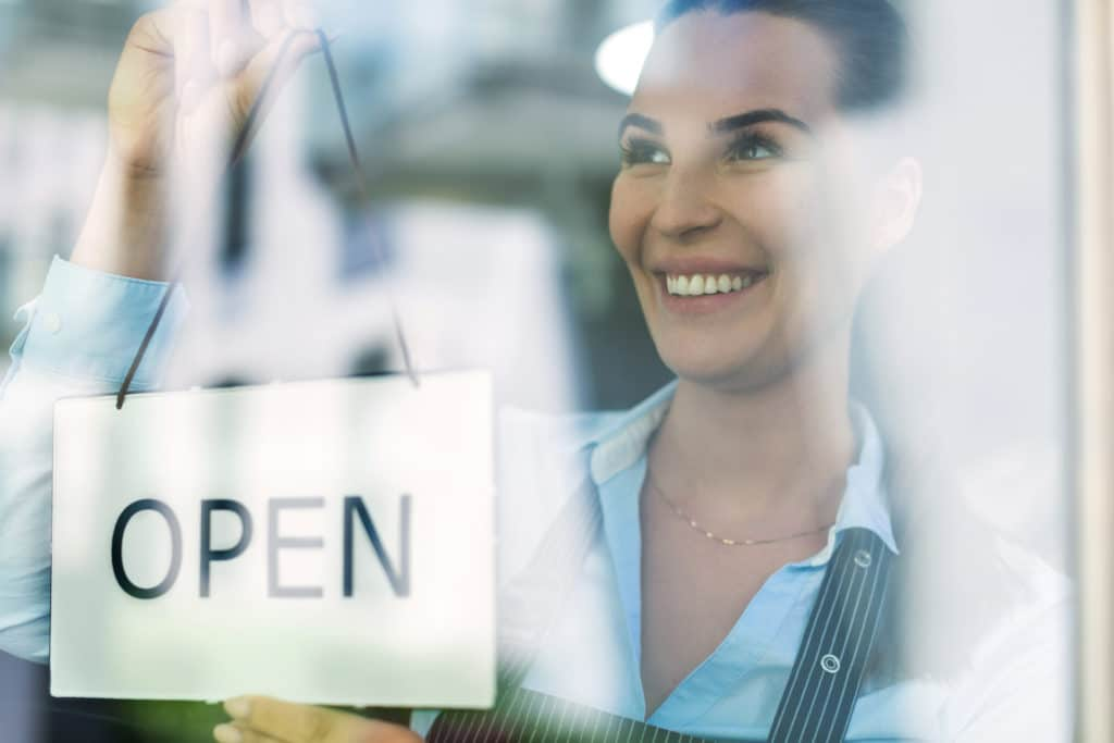 Woman holding open sign in cafe restaurant