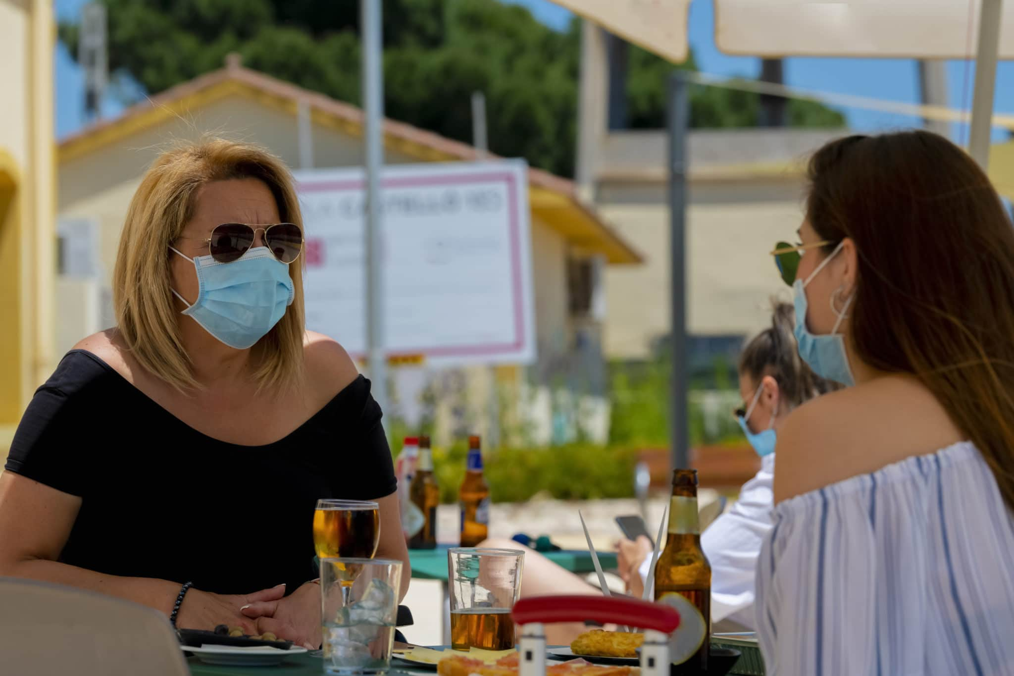 Women using surgical masks and sunglasses sitting at an outdoor bar terrace with beers and snacks on an out of focus background. New lifestyle concept.