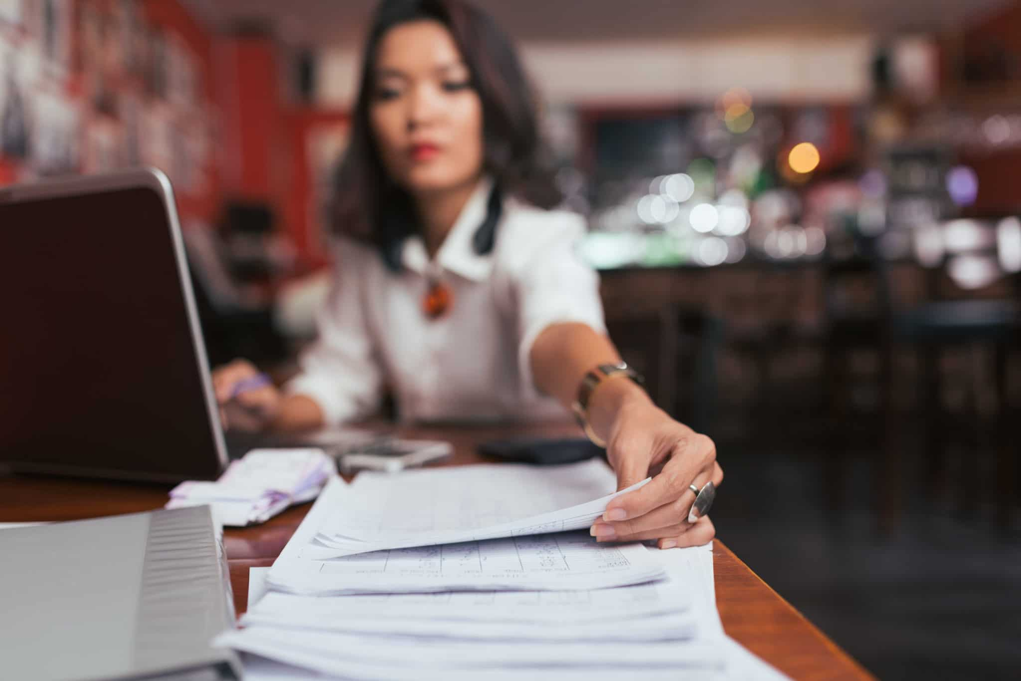Business lady working with financial documents in her bar