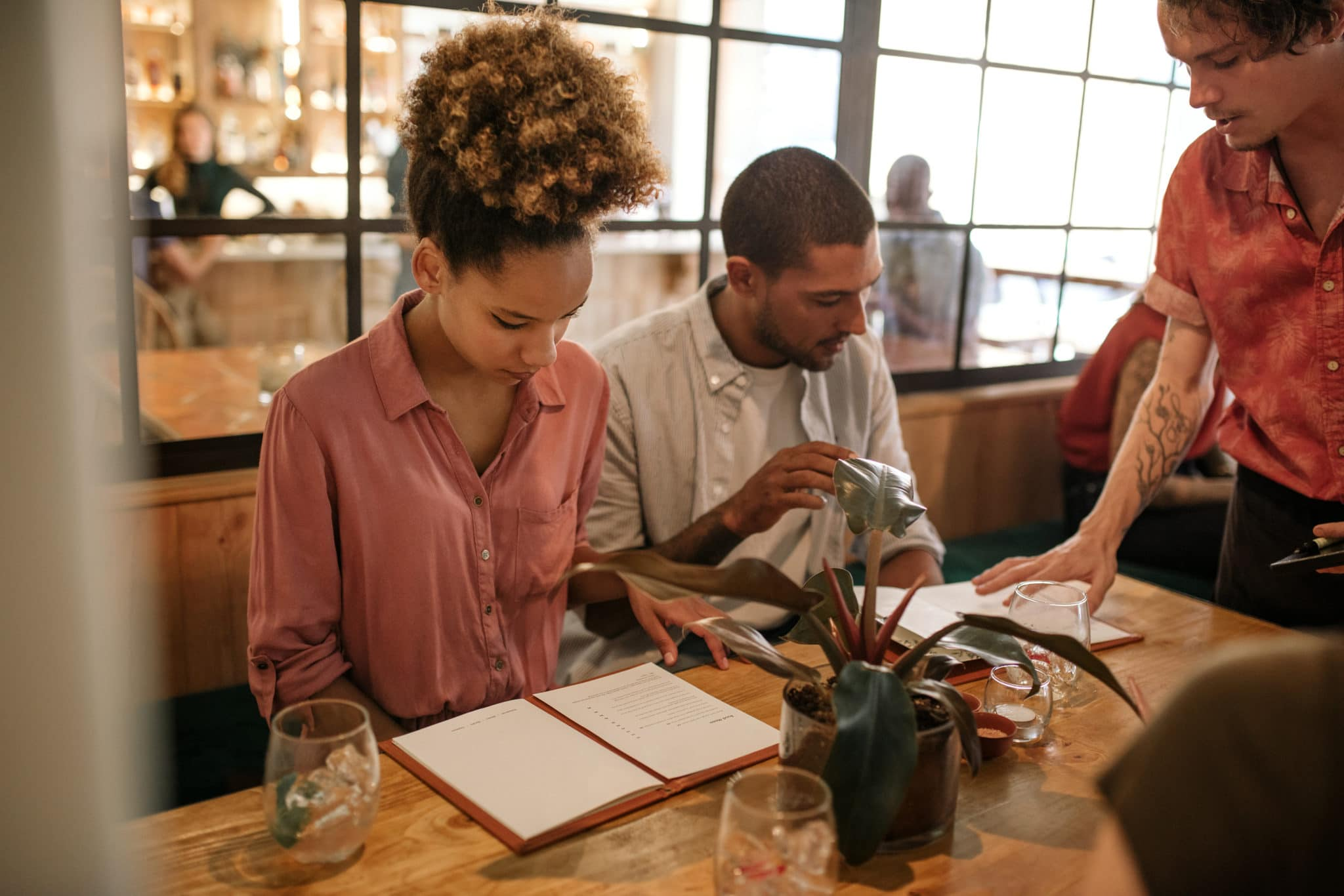 Young woman reading through a menu while sitting with a group of friends at a table in a trendy restaurant