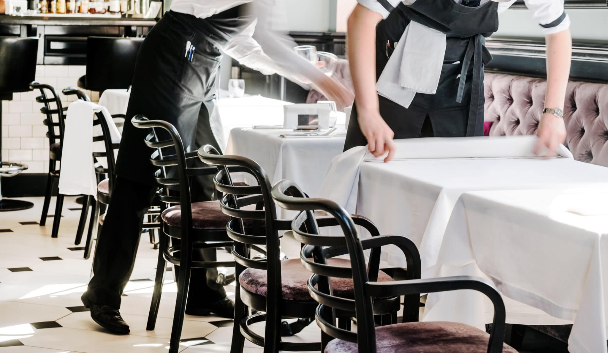 restaurant service putting out tablecloths