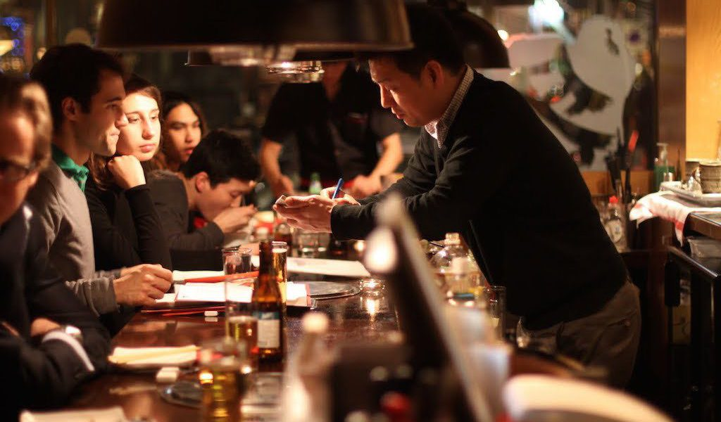 busy restaurant with server and lots of busy tables