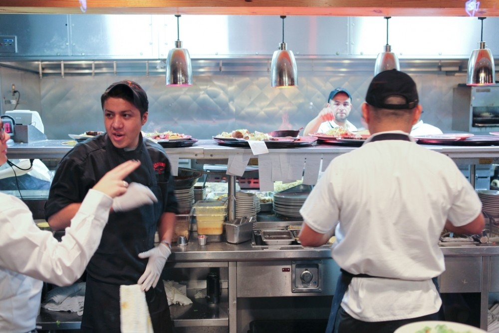 a busy restaurant filled with chefs and cooks