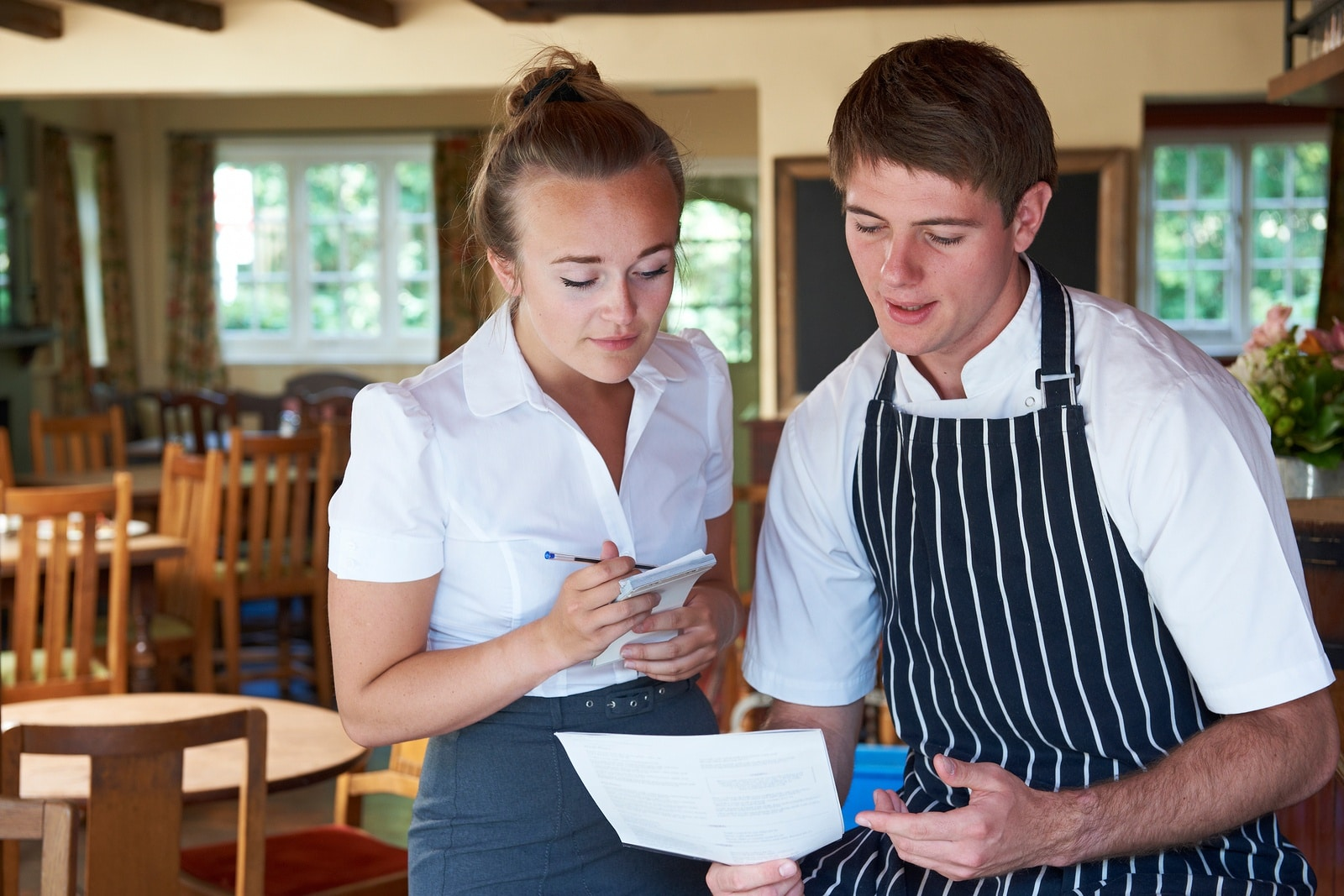 Chef And Waitress Looking Over Their Restaurant Profit Margin