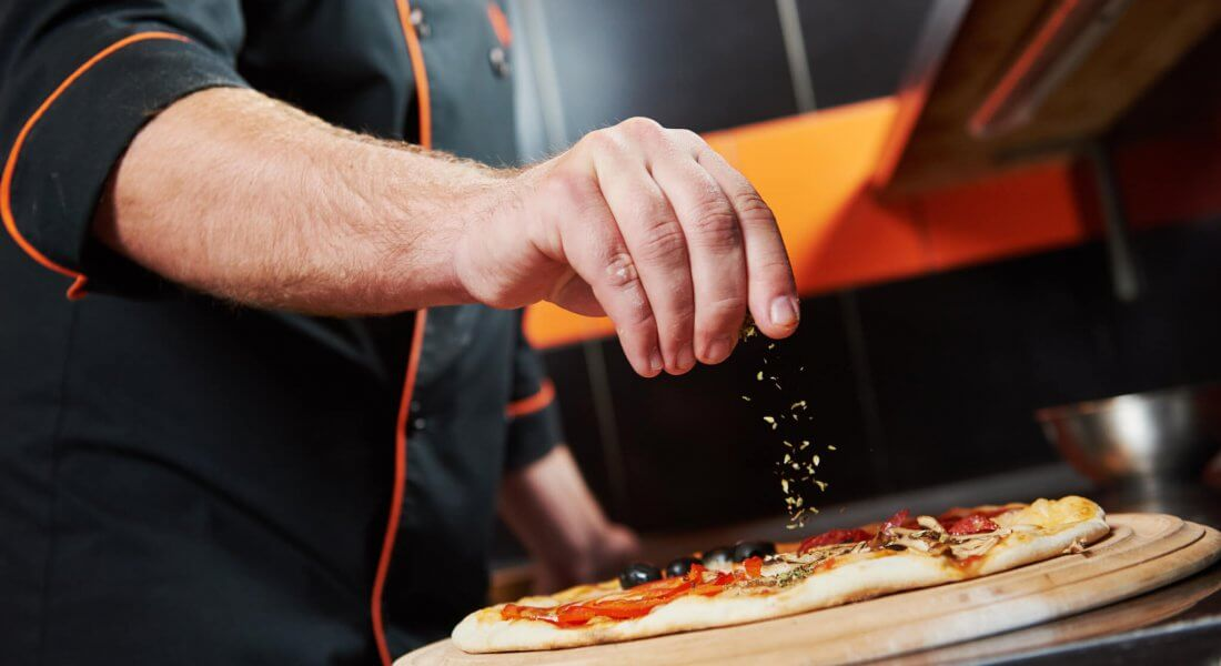 hand of chef baker in uniform adding spice into pizza after pizz