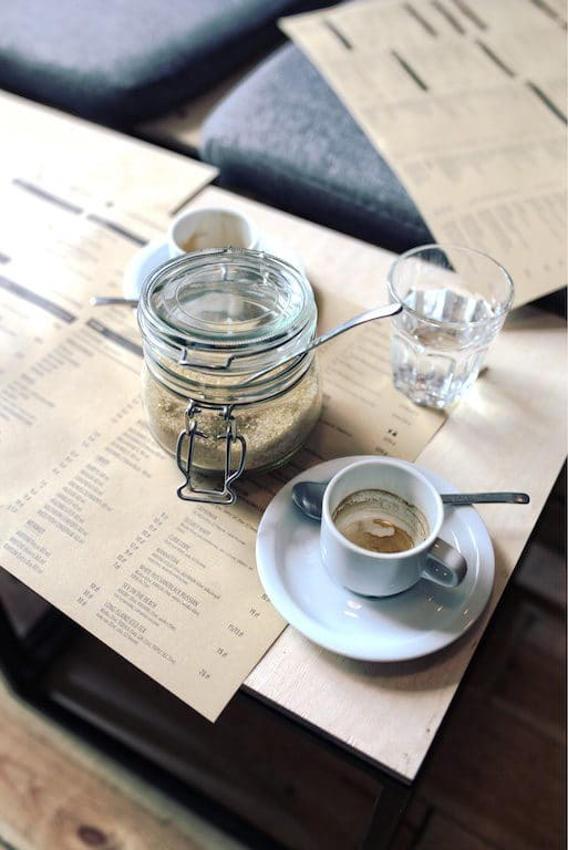 coffee and menu on a table with a sugar pot