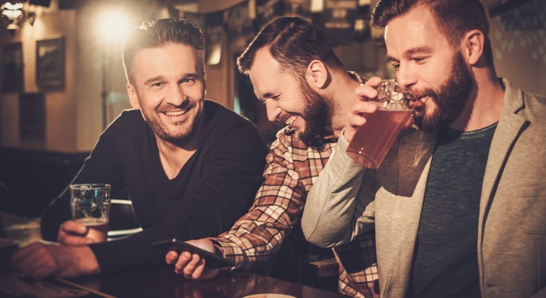 group of friends at a sports bar drinking beers