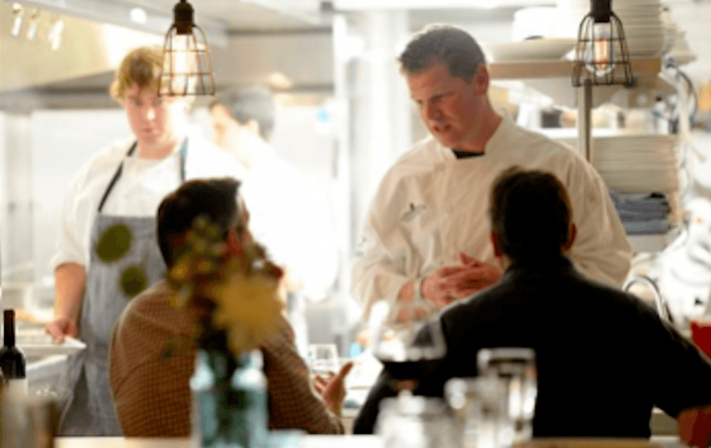 guests talking to a chef in a restaurant