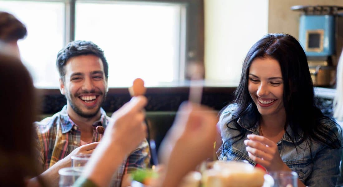guests laughing over a light snack in a restaurant