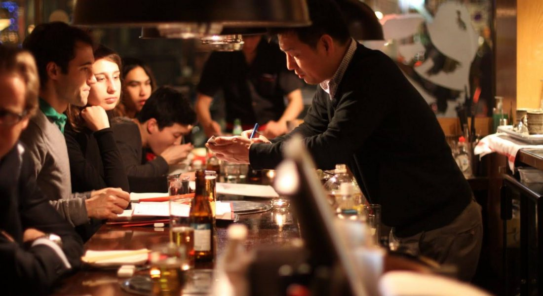 a server in a restaurant helping many guests on a long table