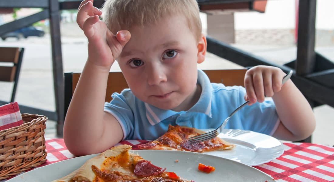 Sweet adorable child boy eating pizza at a restaurant
